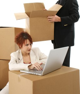 Beautiful thrity something business woman with laptop and cardboard boxes.